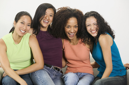 way of behaving: Group of young women looking at camera smiling LANG_EVOIMAGES