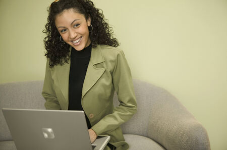irish ethnicity: Young woman sitting on a couch working on a laptop smiling LANG_EVOIMAGES