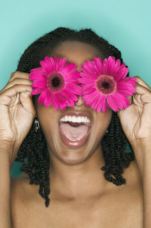 davenport: Young woman holding two flowers in front of her eyes LANG_EVOIMAGES