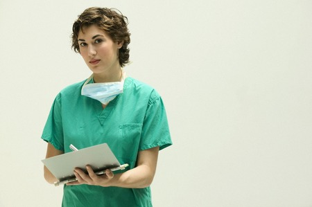 dapper: Female doctor writing in a clipboard