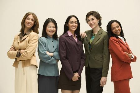 mujeres morenas: Grupo de j�venes empresarias de pie juntos mirando a la c�mara sonriendo