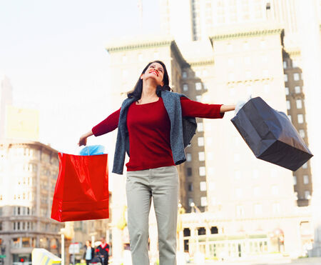 living being: Young woman smiling holding shopping bags LANG_EVOIMAGES