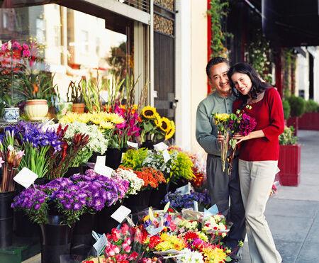 mid adult couple: Mediados de pares de adulto de pie en una tienda de flores