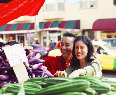 hold ups: Mid adult couple choosing vegetables at a market LANG_EVOIMAGES