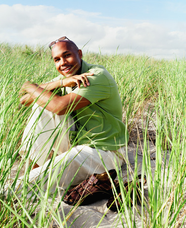 informant: Portrait of a young man squatting on a grassy field