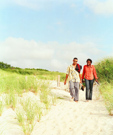 Young couple walking on a sandy trail LANG_EVOIMAGES