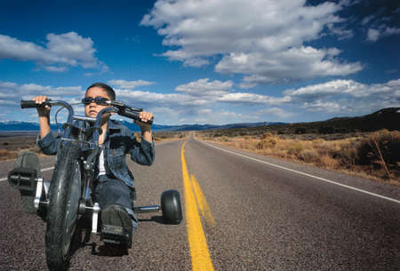 continued: Portrait of a young boy riding a toy motorcycle on a highway