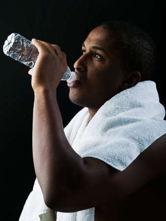 sportsperson: Teenage boy standing with a towel around his neck drinking water from a bottle LANG_EVOIMAGES