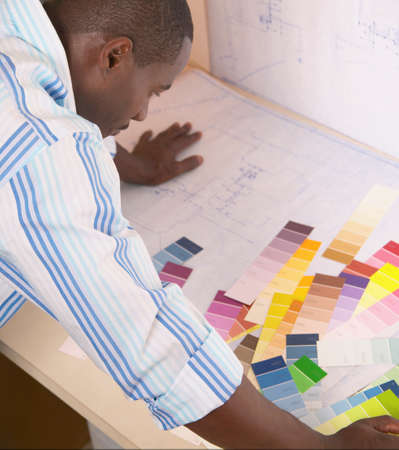preference: Young man leaning over a table looking at color shade samples