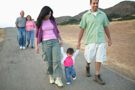 mid adult couple: Mid adult couple walking holding a baby boy with senior couple behind