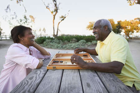 two persons only: Mature couple sitting together playing a board game LANG_EVOIMAGES