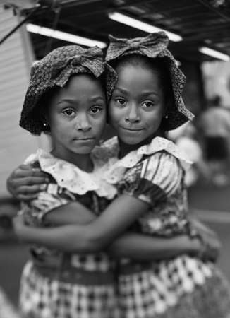 way of behaving: Portrait of young female twins holding each other