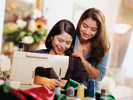 two persons only: Mid adult women using a sewing machine