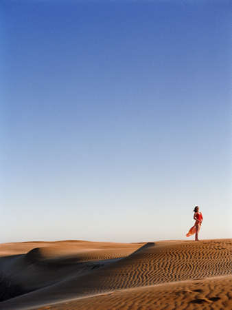 travelled: Mid adult woman standing on a sand dune