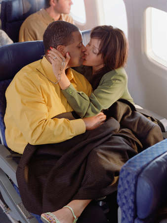 counteract: Couple kissing on an airplane