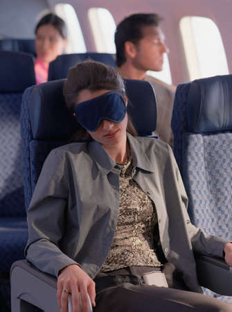 three persons only: Woman sleeping on an airplane LANG_EVOIMAGES