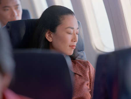 living beings: Woman sleeping in an airplane seat LANG_EVOIMAGES