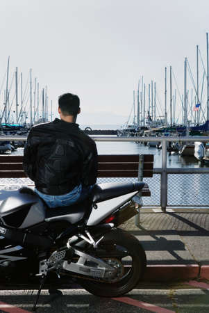 way of behaving: Rear view of a young man sitting on a motorcycle at a dock LANG_EVOIMAGES