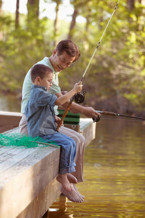 exploratory: Mid adult man and a young child sitting on a pier fishing