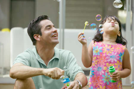 hispanic ethnicity: Young girl and a young man blowing soap bubbles