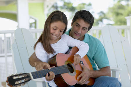 member of the clergy: Young man teaching a young girl to play the guitar