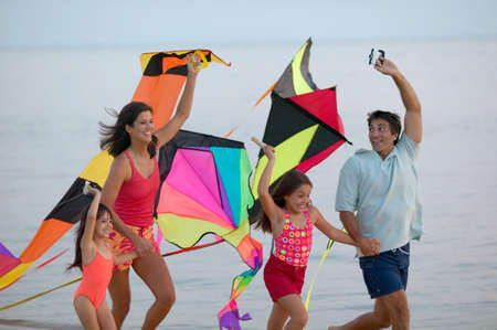member of the clergy: Young couple running on the beach with their children holding kites