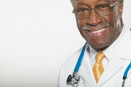 knee bend: Portrait of a senior doctor standing with stethoscope around his neck LANG_EVOIMAGES