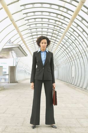 piece of luggage: Portrait of mid adult businesswoman standing holding a briefcase