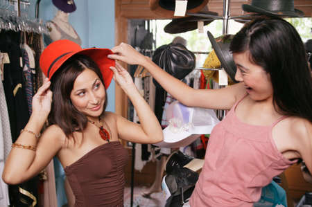 chirpy: Two young women trying a hat in a department store LANG_EVOIMAGES
