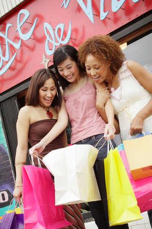 seres vivos: �ngulo de visi�n baja de tres mujeres j�venes con bolsas de la compra
