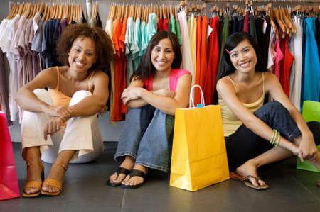 seres vivos: Tres mujeres j�venes sentados en el suelo en una tienda por departamentos