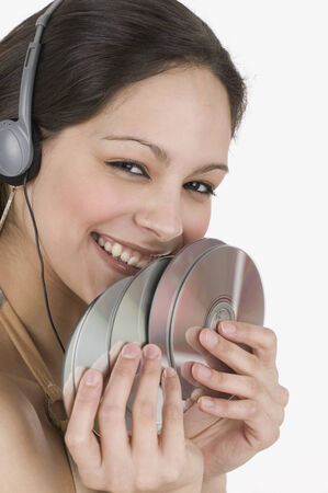 restfulness: Young woman wearing headphones holding compact discs