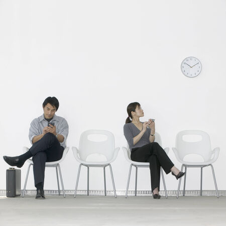 effrontery: Young man and a young woman sitting on chairs operating hand held devices