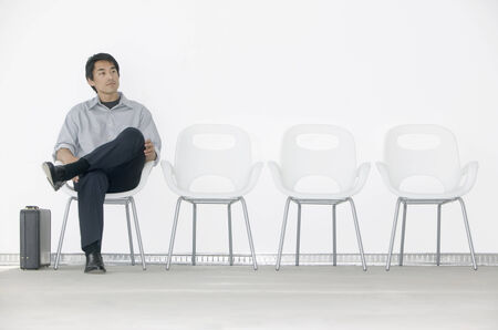 two persons only: Young man sitting on a chair waiting LANG_EVOIMAGES