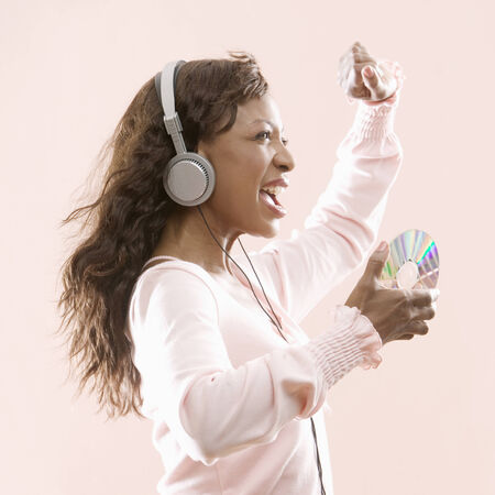 knee bend: Woman wearing headphones holding a compact disc dancing