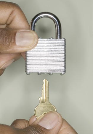 exactitude: Human hands inserting a key into a padlock LANG_EVOIMAGES