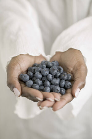 civilized: Womans hands holding blueberries