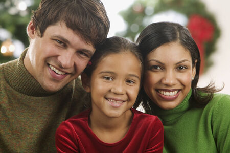 two persons only: Young couple and their child looking at camera smiling with a Christmas tree in the background LANG_EVOIMAGES