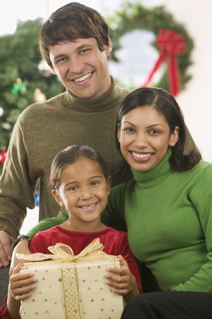 Young couple and their child looking at camera smiling with a Christmas tree in the background LANG_EVOIMAGES