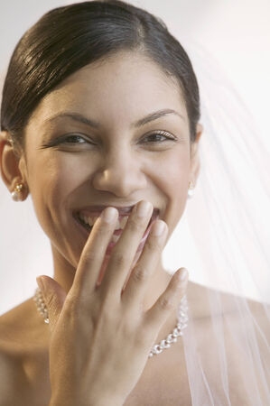 member of the clergy: Young bride smiling with her hand on her mouth looking at camera