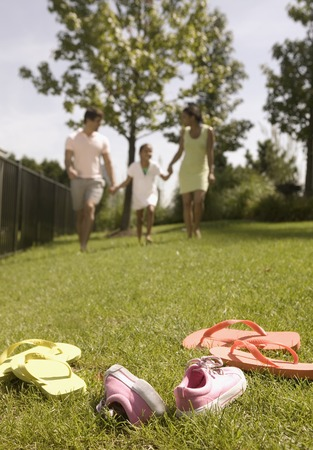 deterrence: Low angle view of a young couple and their child running on a lawn