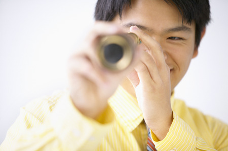 way of behaving: Businessman looking through a telescope smiling