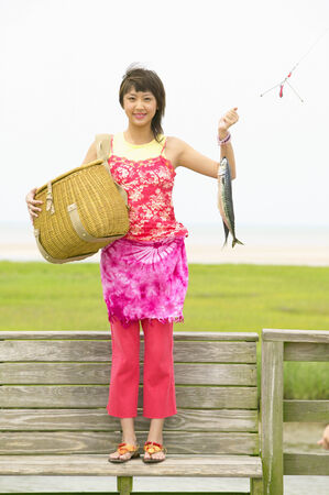 Portrait of a young woman holding a basket and a fish