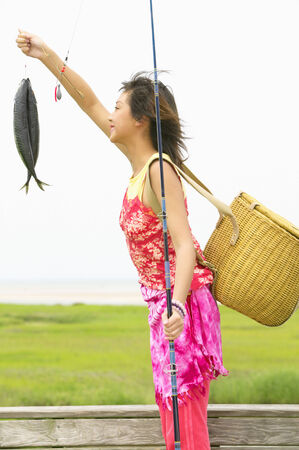 way of behaving: Woman standing holding fish