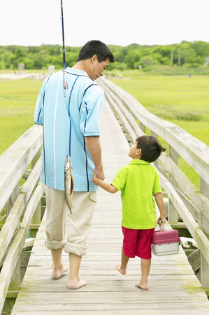 storage bin: Rear view of a father and his son walking on a pier holding fishing gear
