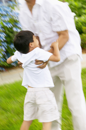 Mid adult man playing with a young boy on a lawn