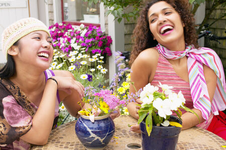 chirpy: Two young women sitting together laughing LANG_EVOIMAGES