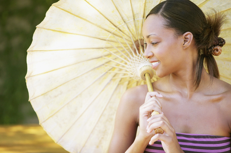 standpoint: Young woman holding a parasol smiling LANG_EVOIMAGES