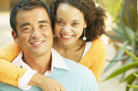 mixed race: Portrait of a young woman holding a mid adult man