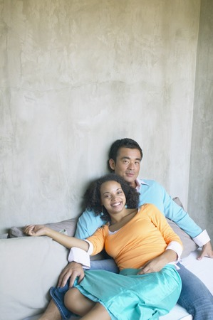 joyousness: Portrait of young couple sitting on bed together